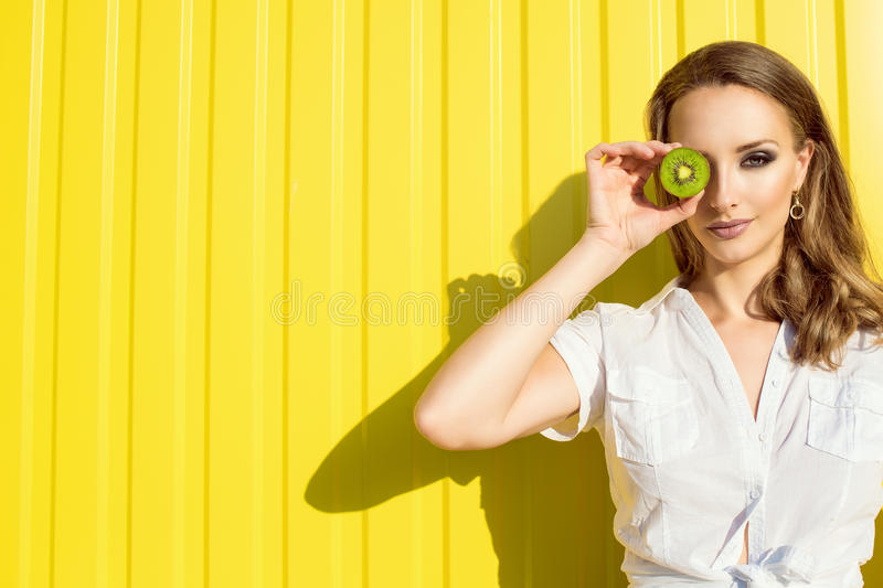 Portrait of beautiful young model with long hair and provocative artistic make-up hiding her eye behind the split kiwi fruit stock image