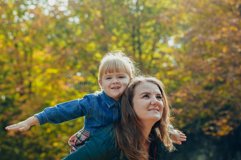 Portrait of a beautiful young mom with a daughter walks in the autumn park. walk and play outdoors royalty free stock photo