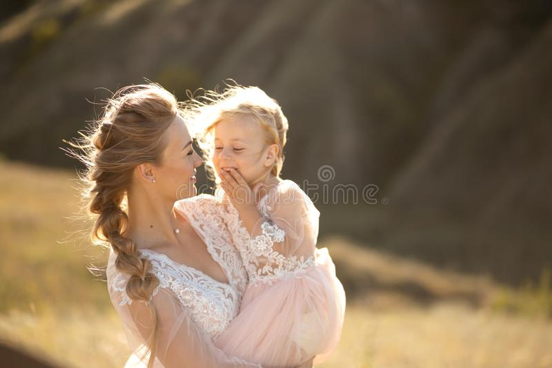 Portrait of a beautiful young mom holds her beloved daughter in her arms. Parental love, little princess stock photos