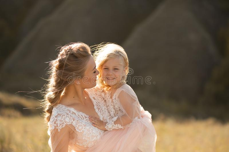 Portrait of a beautiful young mom holds her beloved daughter in her arms. Parental love, little princess stock photography