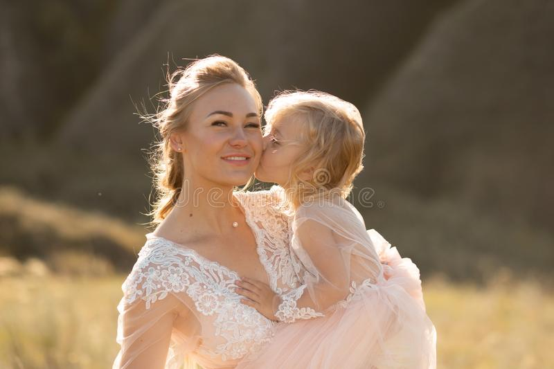 Portrait of a beautiful young mom holds her beloved daughter in her arms. Parental love, little princess stock image
