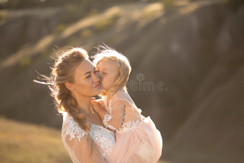 Portrait of a beautiful young mom holds her beloved daughter in her arms. Parental love, little princess royalty free stock photography
