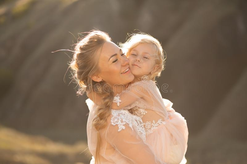 Portrait of a beautiful young mom holds her beloved daughter in her arms. Parental love, little princess royalty free stock images