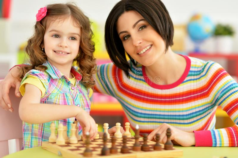 Portrait of beautiful young mother with her cute little daughter playing chess. Beautiful young mother with her cute little daughter playing chess royalty free stock photo