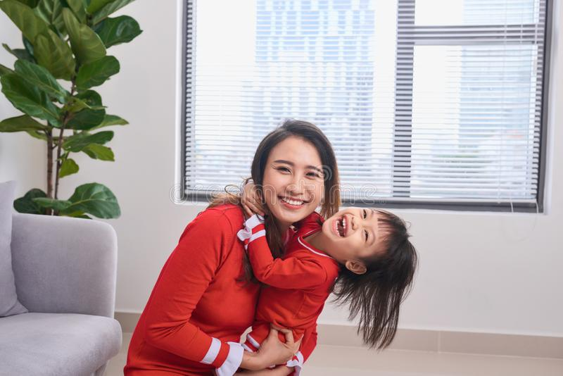 Portrait of beautiful young mother and her daughter hugging, loo royalty free stock photos