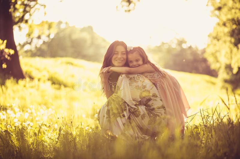 Portrait of beautiful young mother and her daughter at nature. royalty free stock photography