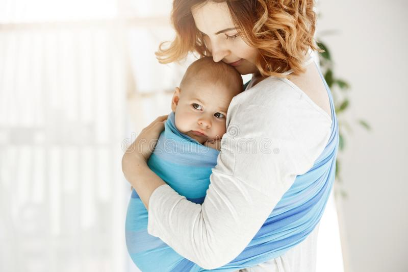 Portrait of beautiful young mother holding tight her newborn baby boy with love and caring. She smiling and feeling royalty free stock photography