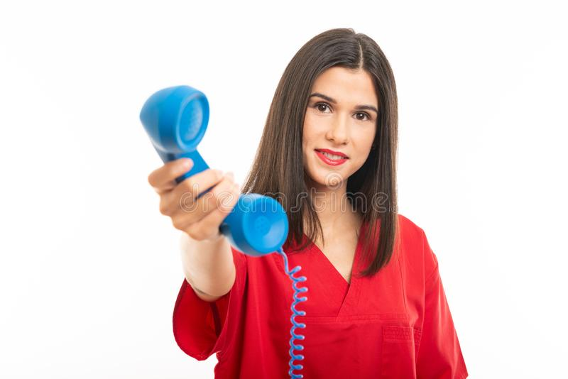 Portrait of beautiful young nurse wearing scrubs handing phone receiver royalty free stock image