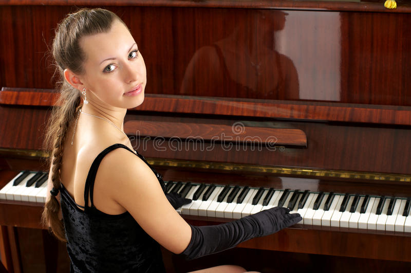 Portrait of beautiful young pianist. Beautiful young female pianist playing some melody royalty free stock images