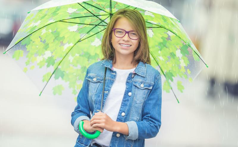 Portrait of beautiful young pre-teen girl with umbrella under spring or summer rain. Smilling girl with dental braces and glasses smile orthodontic teenage royalty free stock photo