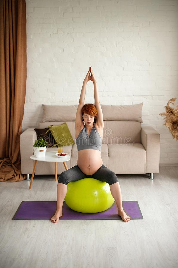Portrait of a beautiful young pregnant woman. Exercises with fitball at home stock photography