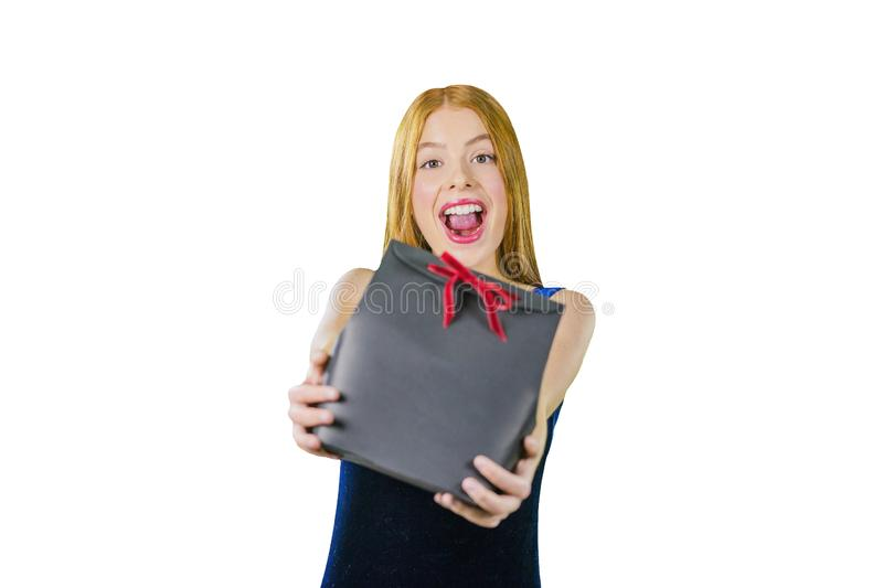 A portrait of a beautiful young red-haired girl in an evening dress who is holding a gift in his arms is smiling stock photography