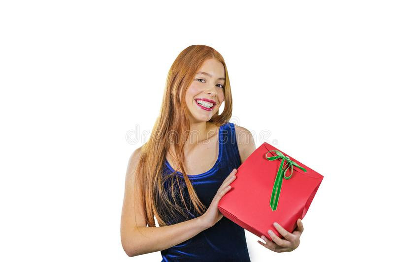 A portrait of a beautiful young red-haired girl in an evening dress who is holding a gift in standing half-turn and royalty free stock images
