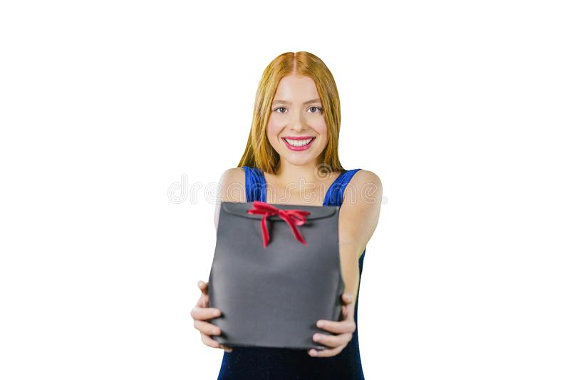 A portrait of a beautiful young red-haired girl in an evening dress who is holding a present in her arms while trying to royalty free stock photo