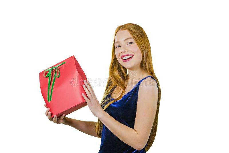 A portrait of a beautiful young red-haired girl in an evening dress who is holding a present is rejoicing and smiling stock photos