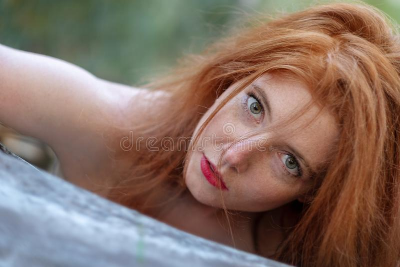 Portrait of a beautiful young red-haired woman with green eyes is sensually leaning against a fallen gray tree trunk stock photo