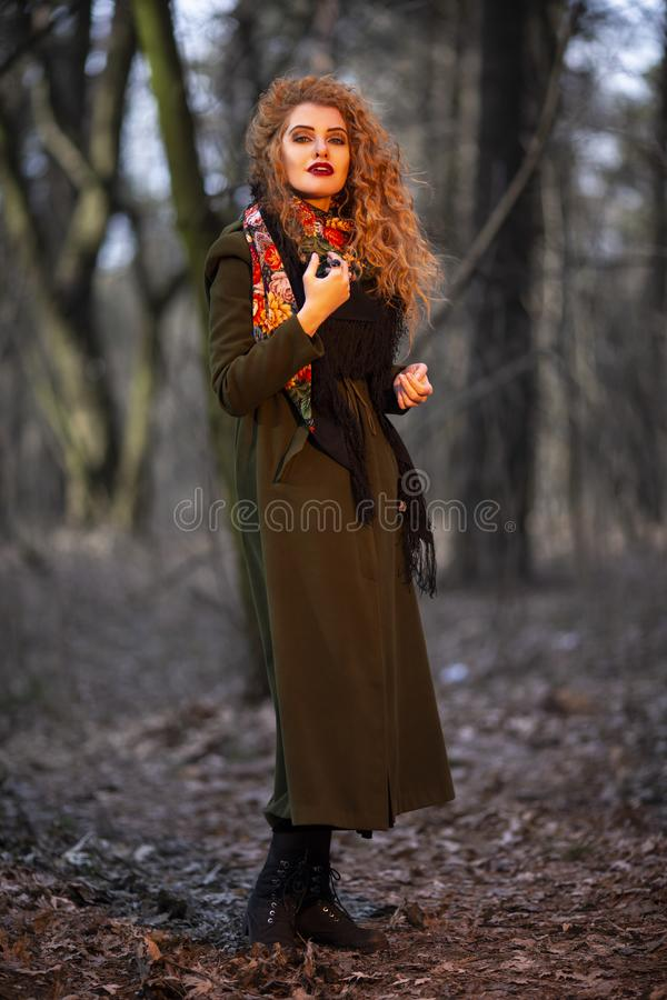 Portrait of Beautiful Young Red Haired Woman In Olive Coat.Posing in Forest Outdoors royalty free stock photo