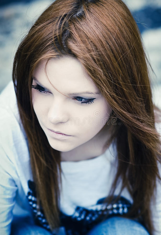 Portrait of beautiful young sad girl in cold tones royalty free stock photography
