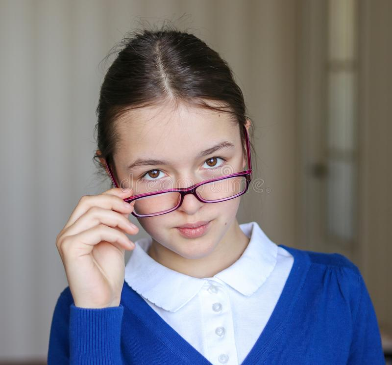 Portrait of beautiful young schoolgirl in school uniform looking over the top of her glasses. stock images
