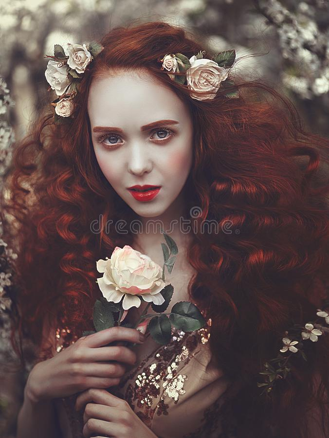 Portrait of a beautiful young sensual woman with very long red curly hair in spring flowers. Colors of spring . stock photos