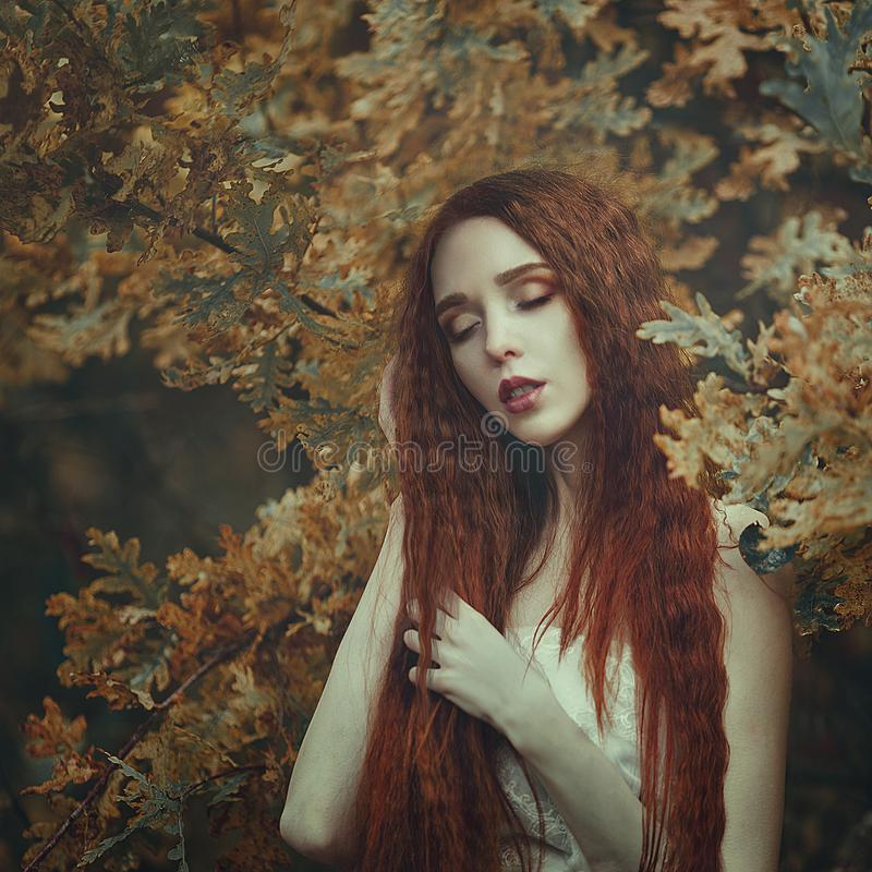 Portrait of a beautiful young sensual woman with very long red hair in autumn oak leaves. Colors of autumn. Creative colors and Artistic processing royalty free stock images