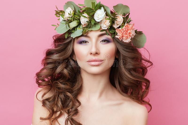 Portrait of beautiful young sexual sensual woman with perfect skin make up curly hair and flowers on head on pink background. Wrea. Th of flowers Spring Summer royalty free stock photography