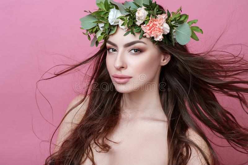 Portrait of beautiful young sexual sensual woman with perfect skin make up streaming hair and flowers on head on pink background. royalty free stock photos