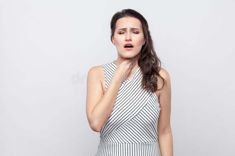 Portrait of beautiful young sick brunette woman with makeup and striped dress standing holding her neck and feeling pain royalty free stock photo