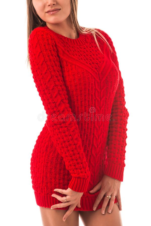 Portrait of a beautiful young slim girl. In a red knitted sweater posing on a white background in the studio. Concept of strong warm knitwear. Advertising space stock photo