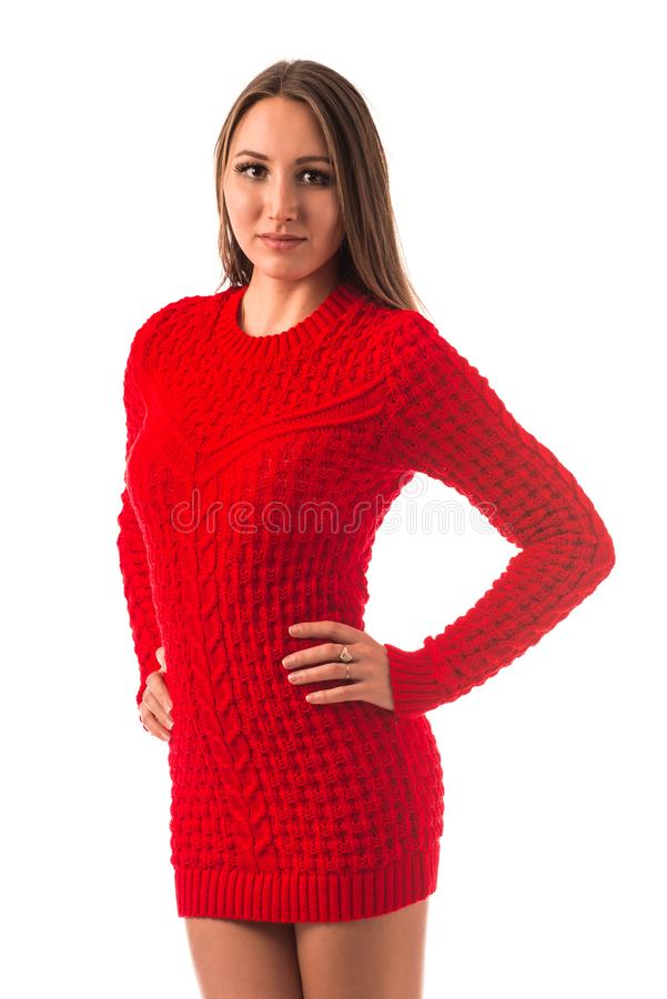 Portrait of a beautiful young slim girl. In a red knitted sweater posing on a white background in the studio. Concept of strong warm knitwear. Advertising space royalty free stock photography