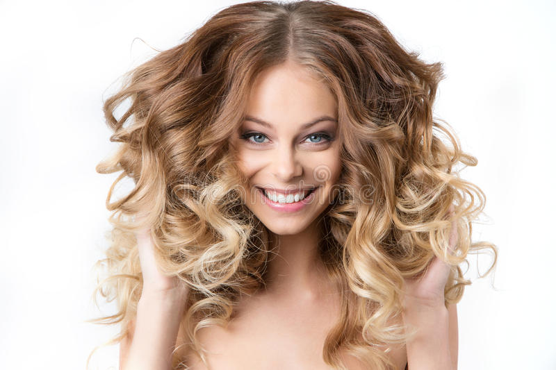 Portrait of beautiful young smiling girl with luxuriant hair curling. stock photos
