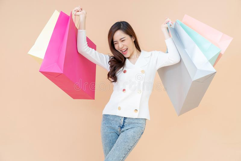 Portrait of Beautiful young smiling happy woman holding shopping bags isolated orange background royalty free stock image