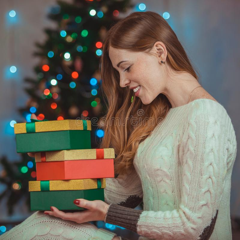 Portrait of a beautiful young smiling woman on a christmas tree background. With gifts in hands royalty free stock photo