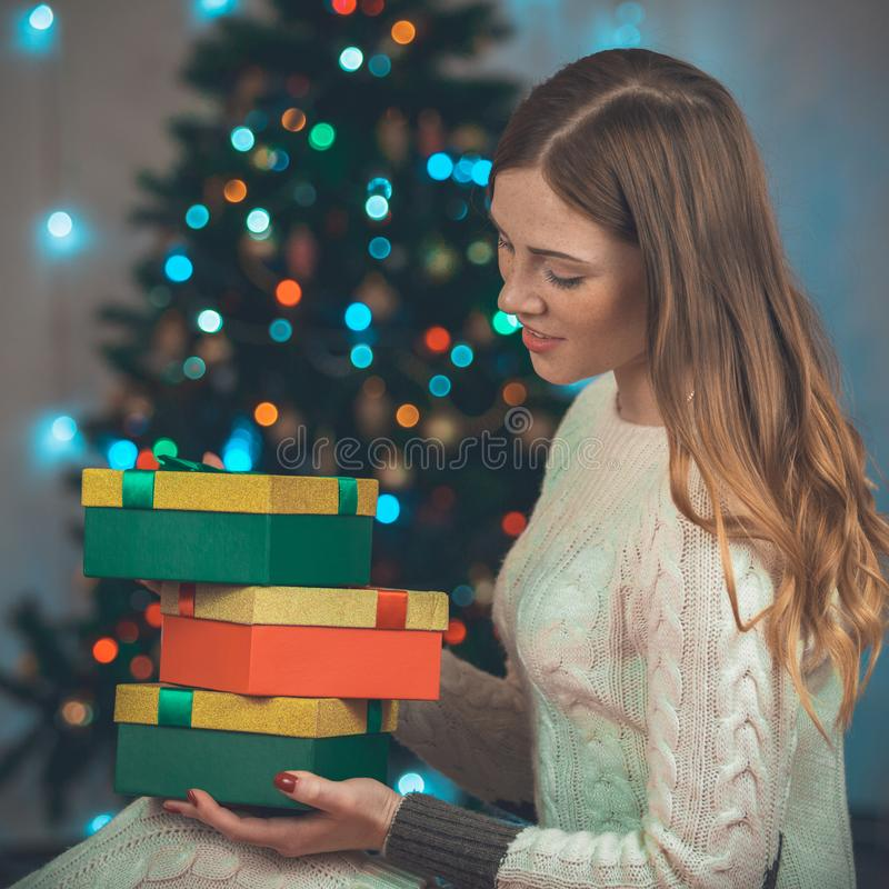 Portrait of a beautiful young smiling woman on a christmas tree background with gifts in hands. Photo indoors stock photography