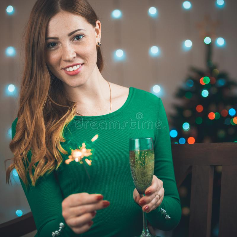 Portrait of a beautiful young smiling woman on a christmas tree background. With a glass of sparkling wine in hands royalty free stock image