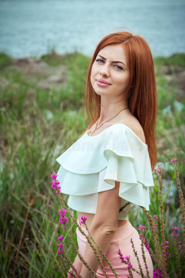 Portrait of beautiful young smiling woman with long red hair stock photo