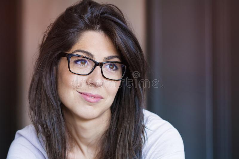 Portrait of Beautiful Young Woman with Modern Eyeglasses. Portrait of beautiful young smiling woman with modern eyeglasses with black frame .Indoor stock image
