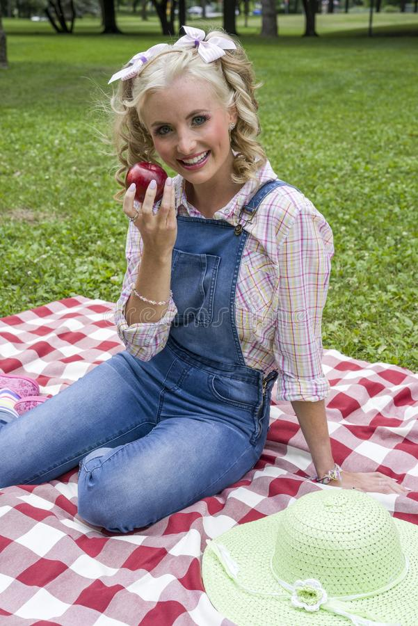 Attractive young blond woman posing outdoors during picnic royalty free stock photos