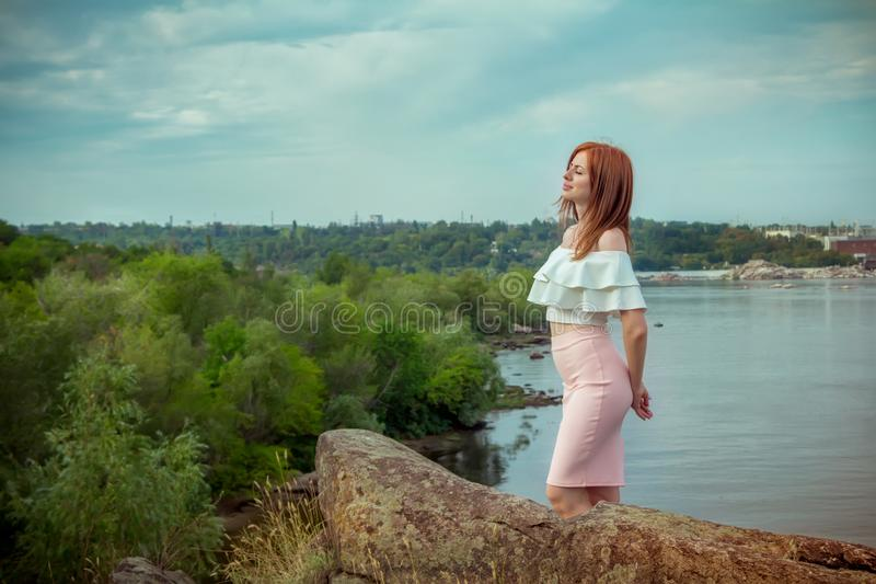 Portrait of beautiful young smiling woman standing on the cliff above the river with her eyes closed stock photo