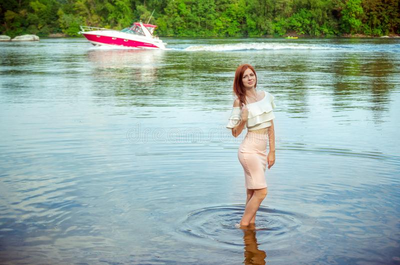 Portrait of beautiful young smiling woman standing in a river water stock photography