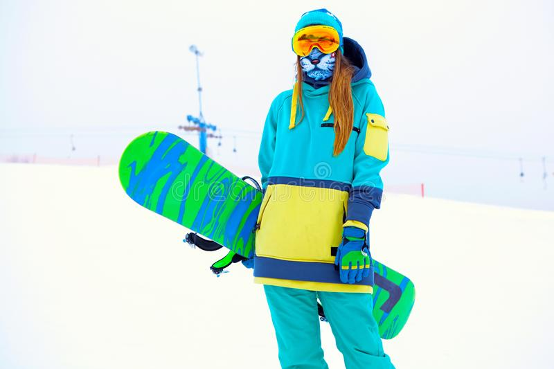 Beautiful young snowboarder girl holding snowboard. Portrait of beautiful young snowboarder girl holding snowboard stock images