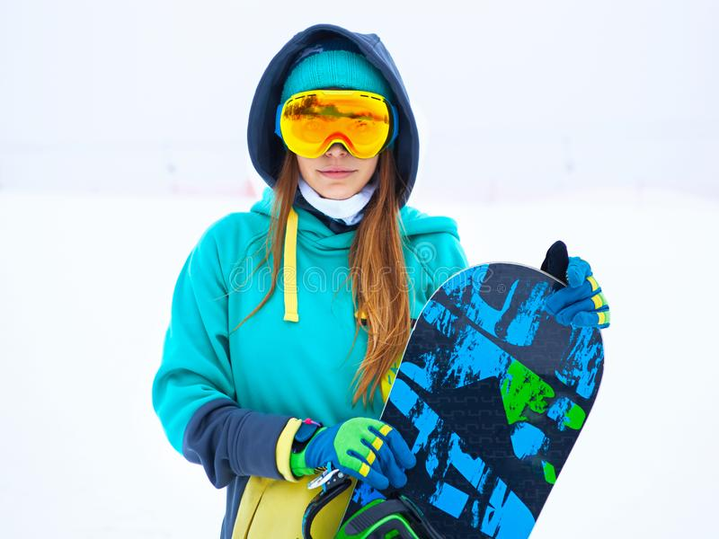 Beautiful young snowboarder girl holding snowboard. Portrait of beautiful young snowboarder girl holding snowboard royalty free stock image
