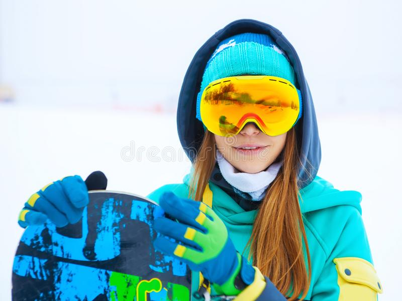 Beautiful young snowboarder girl holding snowboard. Portrait of beautiful young snowboarder girl holding snowboard stock image