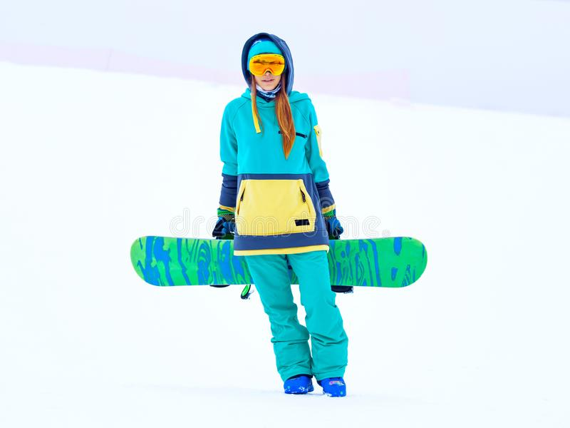 Beautiful young snowboarder girl holding snowboard. Portrait of beautiful young snowboarder girl holding snowboard royalty free stock photo
