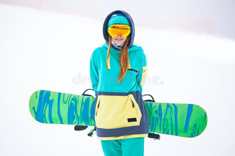Beautiful young snowboarder girl holding snowboard. Portrait of beautiful young snowboarder girl holding snowboard stock photos