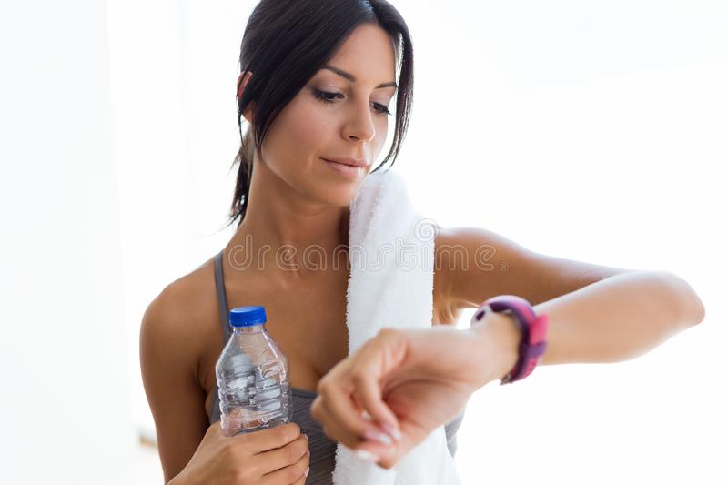 Beautiful young sporty woman looking her smartwatch at home. Portrait of beautiful young sporty woman looking her smartwatch at home royalty free stock photography
