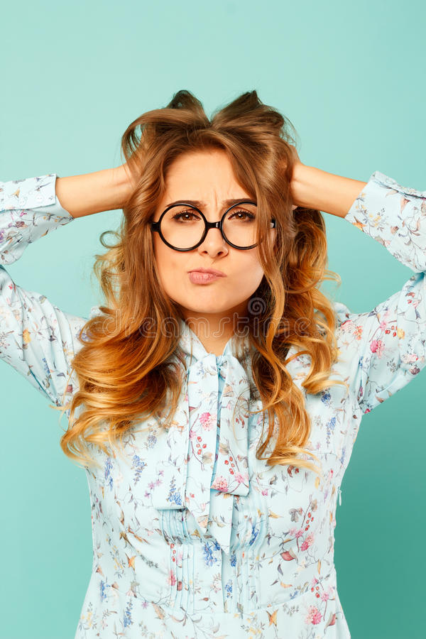 Portrait of a beautiful young student wearing glasses and showing funny emotions on face over blue background. Portrait of a beautiful young student wearing royalty free stock photo