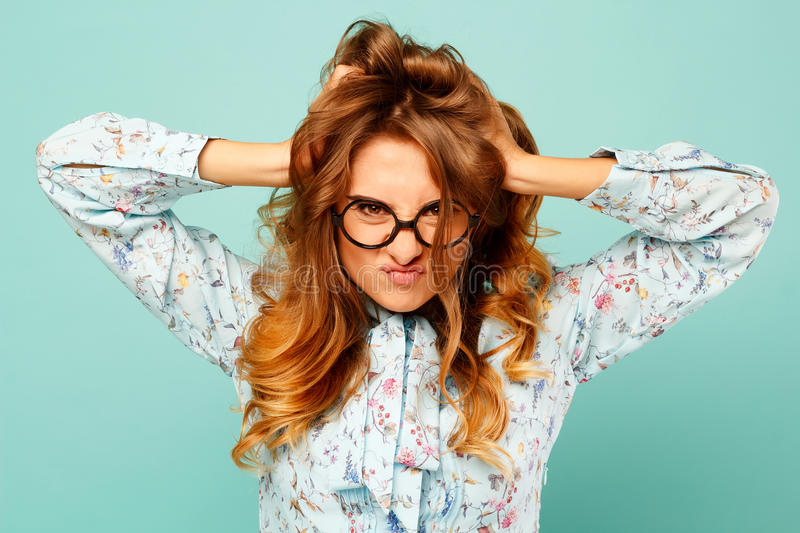 Portrait of a beautiful young student wearing glasses and showing funny emotions on face over blue background. Portrait of a beautiful young student wearing royalty free stock photography
