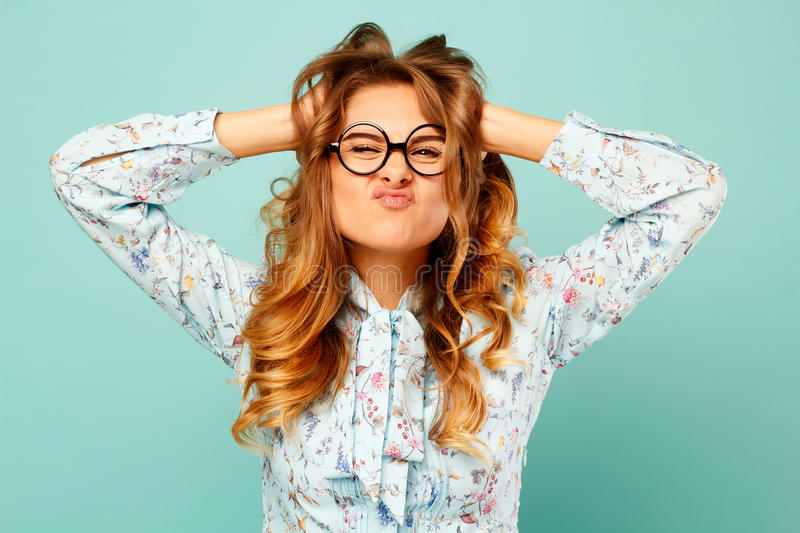 Portrait of a beautiful young student wearing glasses and showing funny emotions on face over blue background. Portrait of a beautiful young student wearing stock image