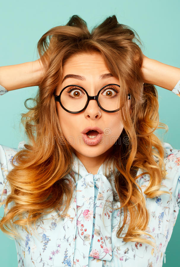 Portrait of a beautiful young student wearing glasses and showing funny emotions on face over blue background. Portrait of a beautiful young student wearing stock photo